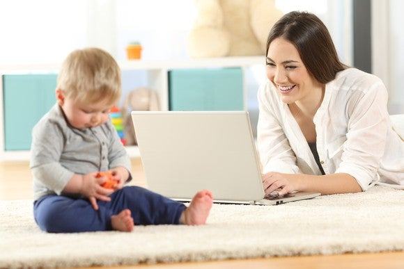 Baby playing with a red toy while his mother smiles at her laptop's screen.