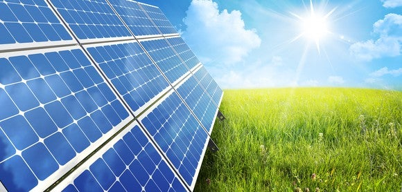 Small solar array on the grass with the sun in the background.