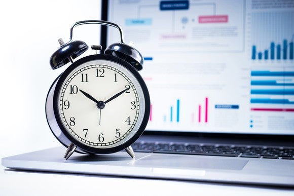 Alarm clock sitting on top of computer.