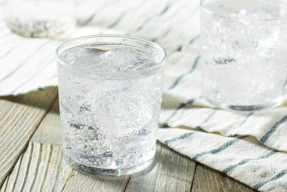 Sparkling water with ice cubes in a glass on a wood-slat table.