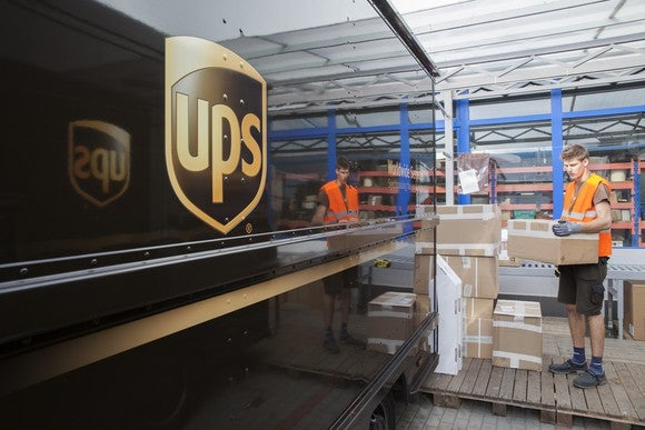 A male UPS employee wearing brown shorts and a neon orange vest loading boxes onto a truck.