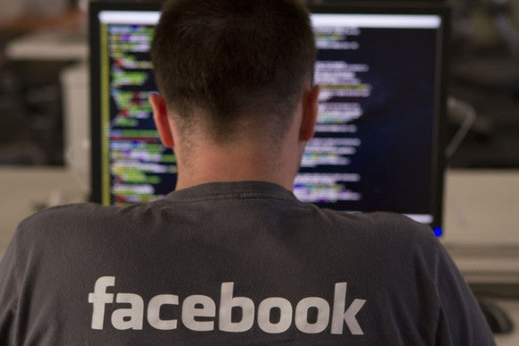 A man in a gray Facebook company T-shirt, with his back turned, writing software code on his computer.