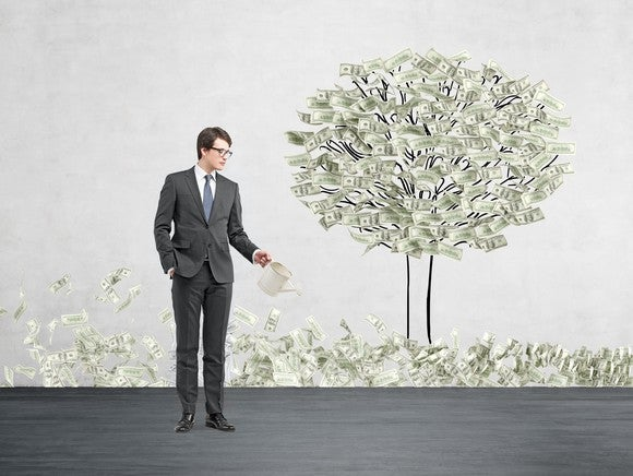A businessman waters a tree made of money.