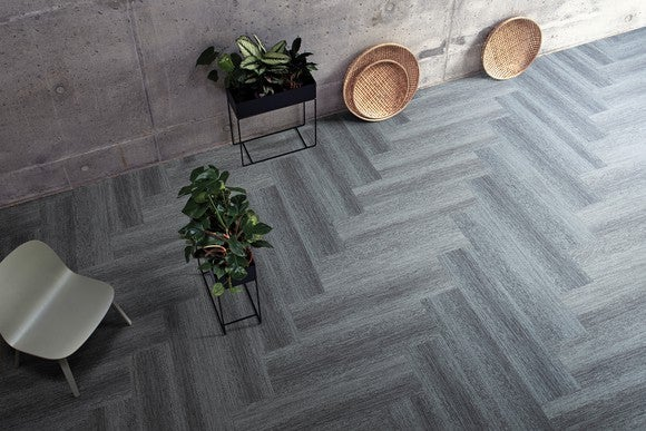 Variegated gray herringbone-style modular flooring by Interface, with two planters, a white chair, and three decorative plates on top.