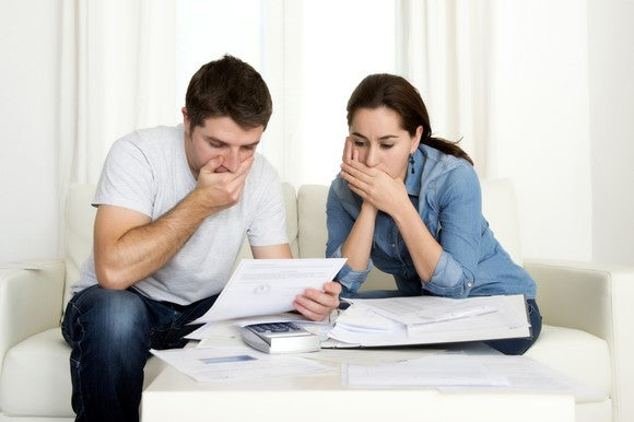 Couple covering their mouths while looking at papers