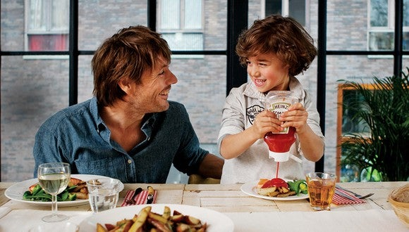 Child squeezing Heinz Ketchup bottle over food while smiling at father at dinner table.