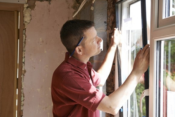 A man installs a new window in a home under renovation