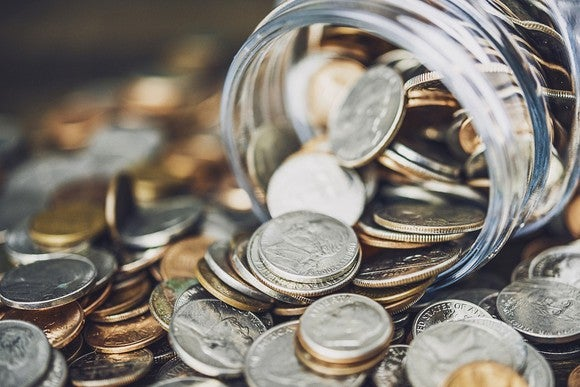 Coins spilling out of a jar and piling up on a flat surface