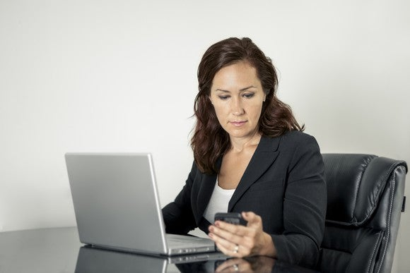 Professional woman looking at a mobile phone as she sits before a laptop at a desk.