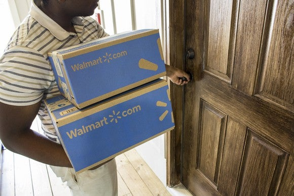 A man holding two Walmart boxes opening a door.