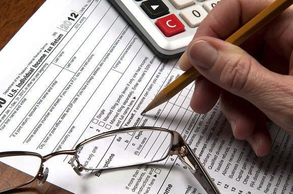 Hand holding a pencil, filling out a paper tax return beside glasses and calculator.