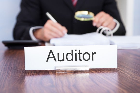 Man with magnifying glass looking over a document with an auditor sign in front of him