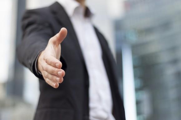 Man in suit extending a handshake