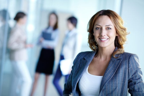 Smiling businesswoman with three other people in the background