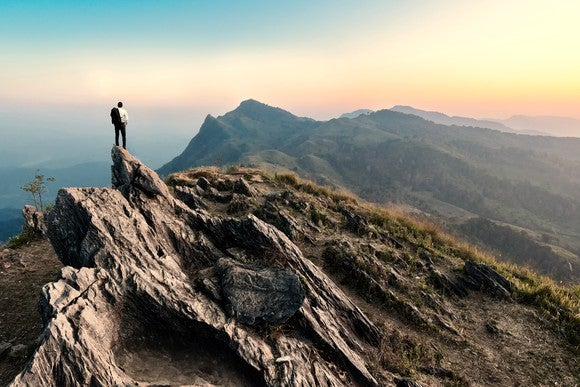 A man standing at the top of a mountain