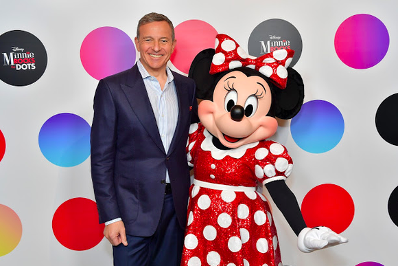 Disney CEO Bob Iger and Minnie Mouse pose in front of a polka-dotted backdrop.
