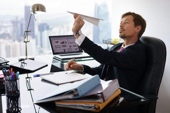 a man in a suit in an office aims a paper airplane.