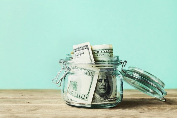 Sitting on a wooden surface, a clear glass jar with its lid open is filled with hundred dollar U.S. bills