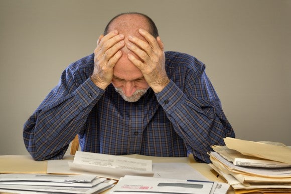 Senior man, with both hands holding his head, poring over stacks of papers, looking concerned.