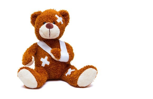 Sitting teddy bear with bandages and wearing a sling on its arm.