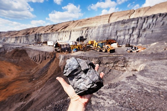 A hand holding up a piece of coal in an open pit mine.