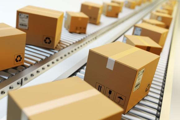 Sealed cardboard boxes riding on a conveyor belt.