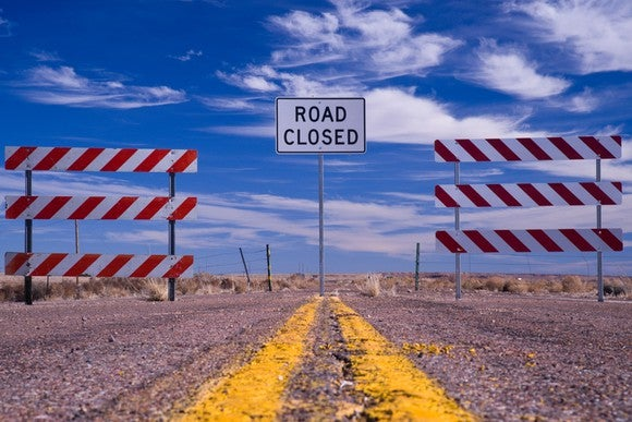 A road closed sign between two barricades on a rural road.