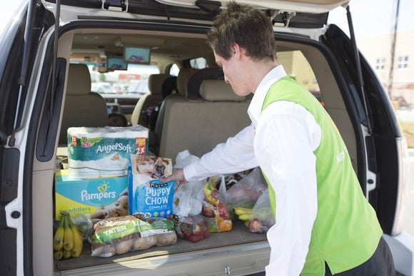 A Walmart associate loading groceries and other items into a customer's car.
