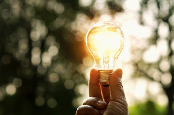 A light bulb being held in the sunlight.