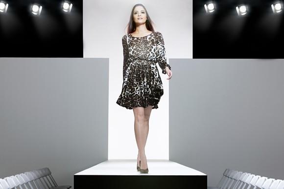 A model in a leopard-print dress walks a runway.