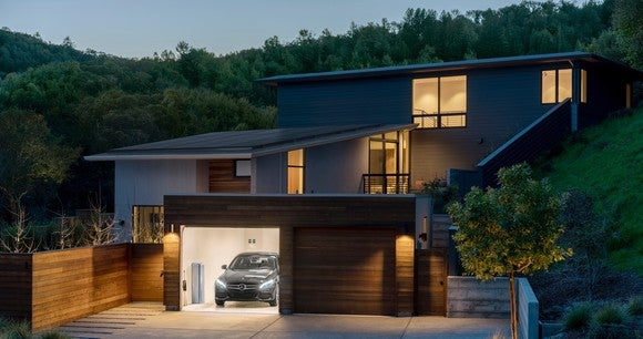 A house with a solar roof and an energy storage system in the garage.