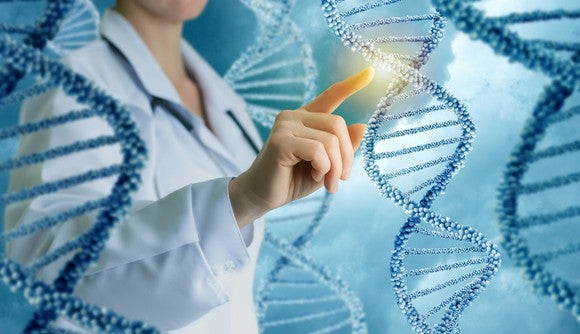 A woman in a lab coat pointing to the backbone of a  DNA double helix molecule.