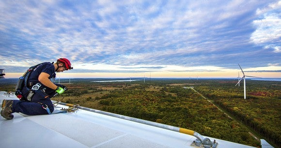 Worker on top of wind turbine looking at landscape with multiple windmlls in sight.
