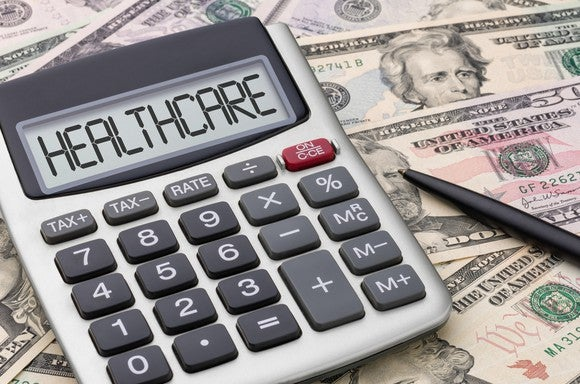 """Calculator displaying """"healthcare"""" on screen on top of cash"""
