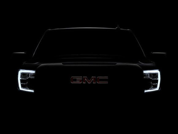 A darkened photo of the front end of the new GMC Sierra.