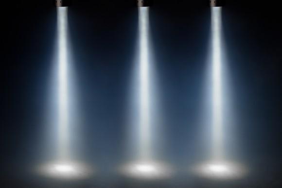 Three bright spotlights shining down on a dark stage.