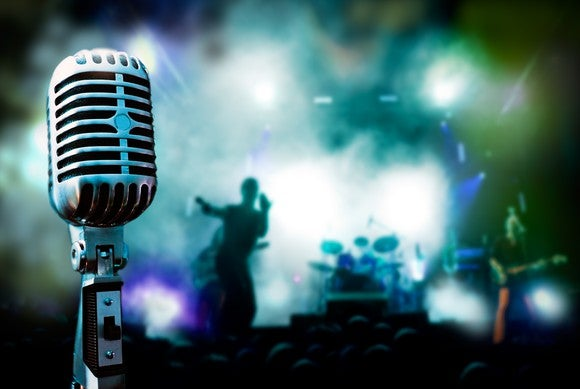 Close-up view of a vintage microphone, with a live music show happening in the background.