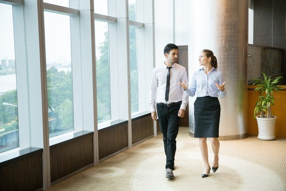Professional man and woman walking and talking in an office.