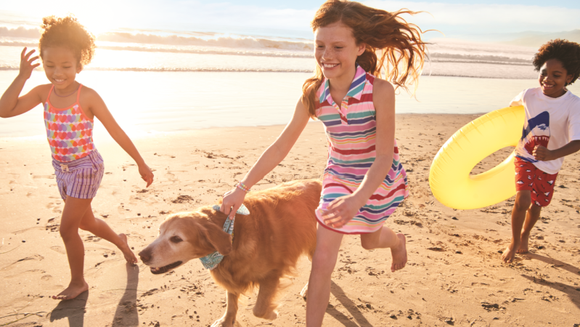 Kids running on beach with dog