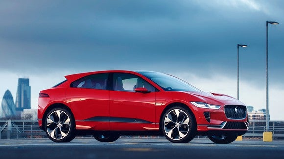 A red Jaguar I-Pace, a sleek red SUV with elements of sports-sedan styling.