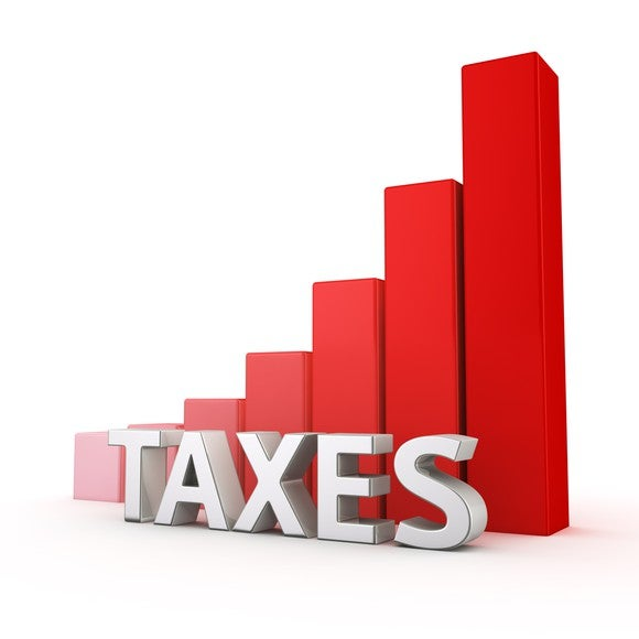 The word taxes in front of an upward bar graph