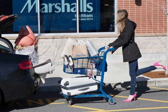 A woman with a fully-loaded shopping cart in front of a Marshalls store.
