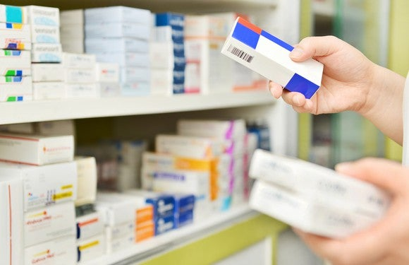 Person holding medications in front of a shelves with stacked medicine packs