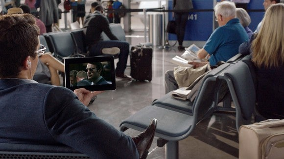 Man in the airport streaming video on a tablet.
