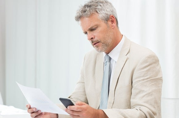 Senior man in a suit looking at a phone and a document