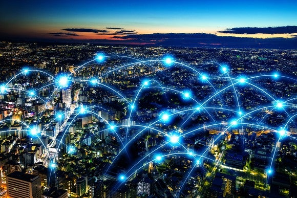 Connectivity network depicted by glowing web connecting various buildings in a city.