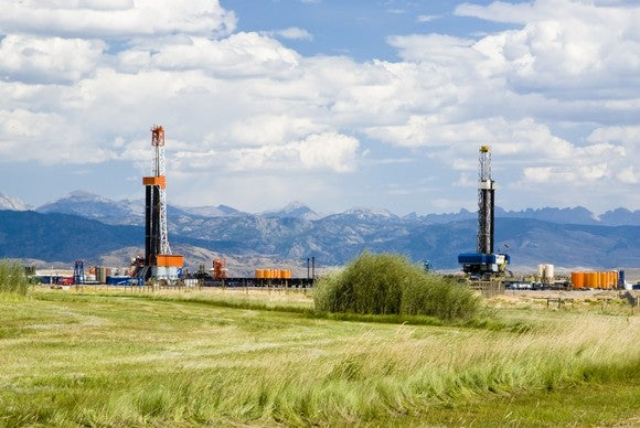 Drilling rigs against a backdrop of mountains