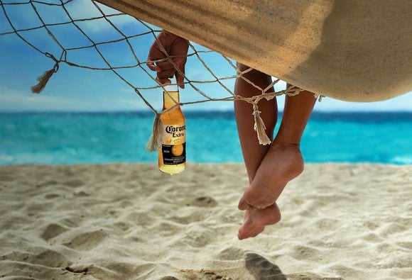 Person holding a bottle of Corona with feet hanging off the side of a hammock.