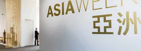 White wall with Asia Week in gold lettering, with a few exhibits behind a veil.