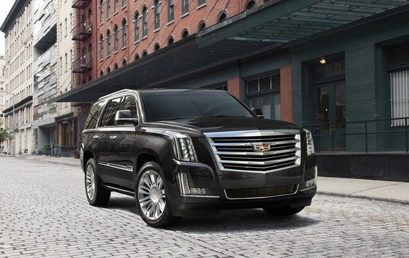 A black Cadillac Escalade, a large SUV, parked on a New York City street.